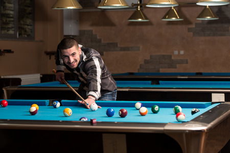 pool hall: Young Man Playing Billiards Lined Up To Shoot Easy Winning Shot Stock Photo