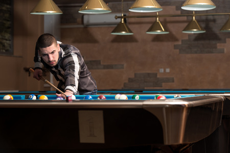 pool hall: Young Man Lining To Hit Ball On Pool Table Stock Photo