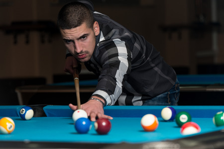 carves: Young Man Playing Billiards Lined Up To Shoot Easy Winning Shot Stock Photo
