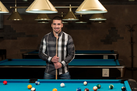 pool hall: Portrait Of A Young Man Playing Billiards