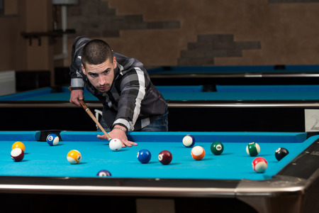 billiards hall: Young Man Lining To Hit Ball On Pool Table Stock Photo