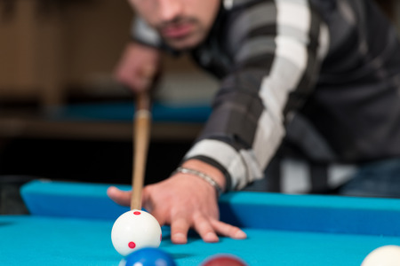 carves: Young Man Lining To Hit Ball On Pool Table Stock Photo