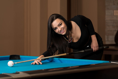 carves: Young Woman Playing Billiards Lined Up To Shoot Easy Winning Shot Stock Photo