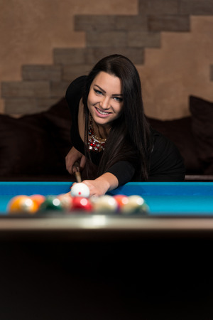 billiards hall: Young Woman Playing Billiards Lined Up To Shoot Easy Winning Shot Stock Photo