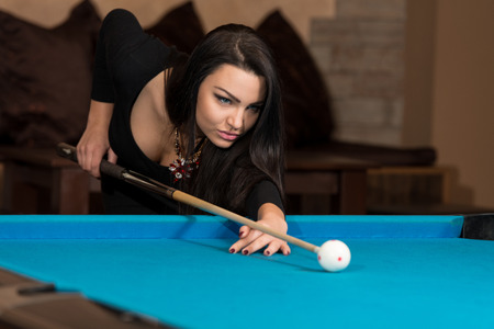 pool hall: Young Woman Lining To Hit Ball On Pool Table Stock Photo