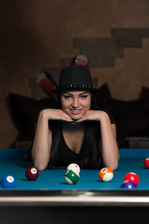 pool hall: Portrait Of A Young Woman Lying On The Table And Playing Billiards Stock Photo