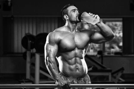 hombre deportista: Hombre muscular que bebe una botella de agua Foto de archivo