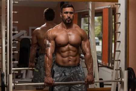 trapezius: Bodybuilder Doing Heavy Weight Exercise For Trapezius