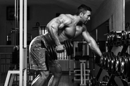 Mexikanische Bodybuilder tun Heavy Weight Übung für Rücken Mit Dumbbells Standard-Bild