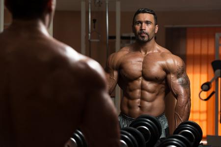 culturista: Am�rica Bodybuilder est� resolviendo Biceps - flexiones de concentraci�n con mancuernas Foto de archivo