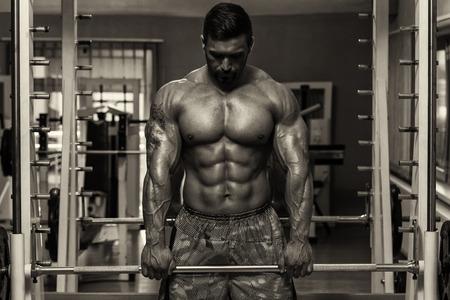 trapezius: Bodybuilder Doing Heavy Weight Exercise For Trapezius