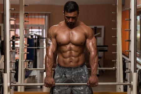 trapezius: Bodybuilder que hace Heavy Weight Ejercicio Para Trapecio