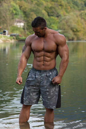 Attractive Man Standing In River And Enjoys The Nature