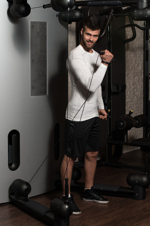man exercise: Young Handsome Man Exercise Biceps On Machine Stock Photo