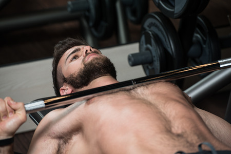 hairy chest: Handsome Man Is Working Out Chest With Barbell In A Modern Gym