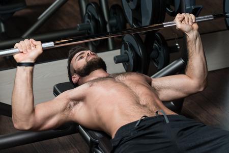 niño sin camisa: Hombre Hermoso Se Está Resolviendo el pecho con pesas en un gimnasio moderno Foto de archivo
