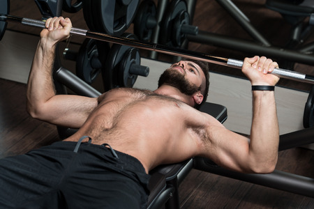 well build: Handsome Man Is Working Out Chest With Barbell In A Modern Gym