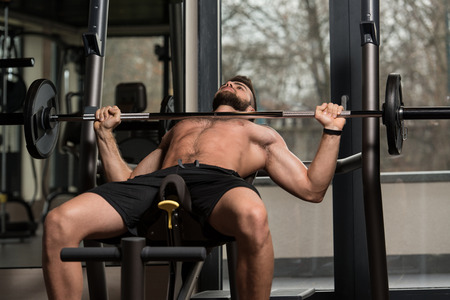 Handsome Man Is Working Out Chest With Barbell In A Modern Gym photo