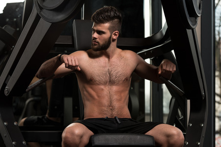 Handsome Man Is Working Out Chest On Machine In A Modern Gym photo