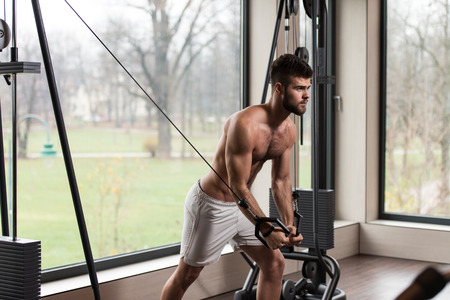 well build: Handsome Man Is Working On His Chest With Cable Crossover In A Modern Gym