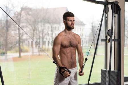 hairy chest: Handsome Man Is Working On His Chest With Cable Crossover In A Modern Gym