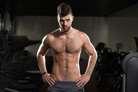 niño sin camisa: Retrato de una joven deportiva Hombre en el moderno gimnasio con aparatos de gimnasia Foto de archivo