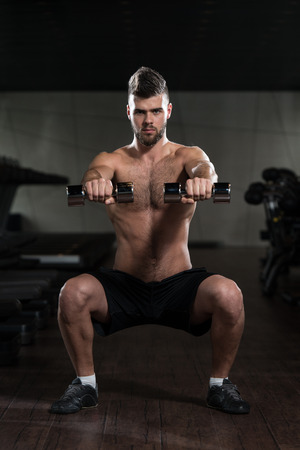 Young Man Performing Dumbbell Squats - One Of The Best Bodybuilding Exercise For Legs photo