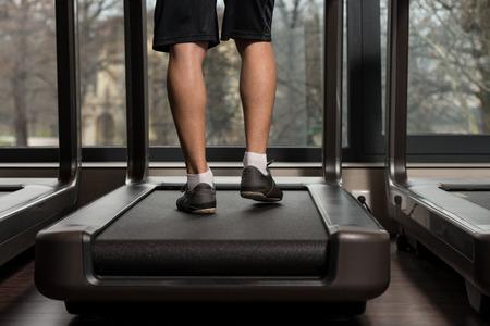 piernas hombre: Cerca de las piernas de hombre corriendo en la cinta - Movimiento borroso Foto de archivo