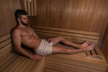 bathhouse: Happy Good Looking And Attractive Young Man With Muscular Body Relaxing In Sauna Hot Stock Photo
