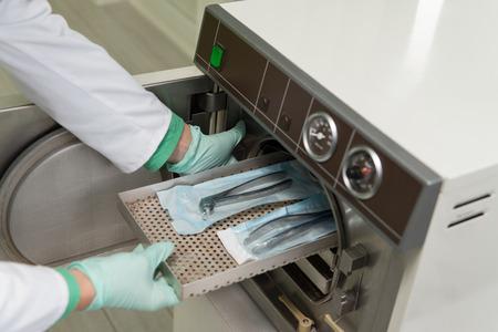 Young Female Dentist Orte Medizinische Autoklav zum Sterilisieren Chirurgische und andere Instrumente Standard-Bild