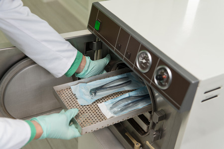 Young Female Dentist Places Medical Autoclave For Sterilising Surgical And Other Instruments Stock Photo