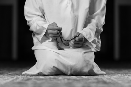 islamic pray: Young Muslim Man Making Traditional Prayer To God While Wearing A Traditional Cap Dishdasha Stock Photo