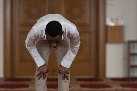 african business man: Black African Muslim Man Is Praying In The Mosque Stock Photo