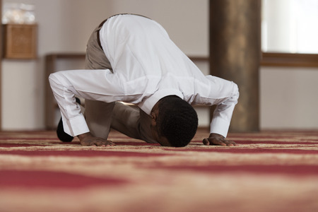 african worship: Black African Muslim Man Is Praying In The Mosque Stock Photo