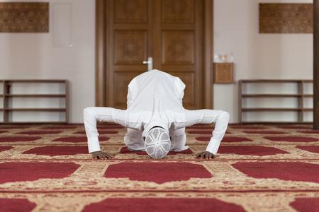 afro arab: African Muslim Man Making Traditional Prayer To God While Wearing A Traditional Cap Dishdasha