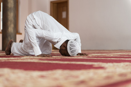 worship white: African Muslim Man Making Traditional Prayer To God While Wearing A Traditional Cap Dishdasha