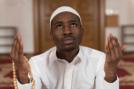 islamic pray: African Muslim Man Making Traditional Prayer To God While Wearing A Traditional Cap Dishdasha