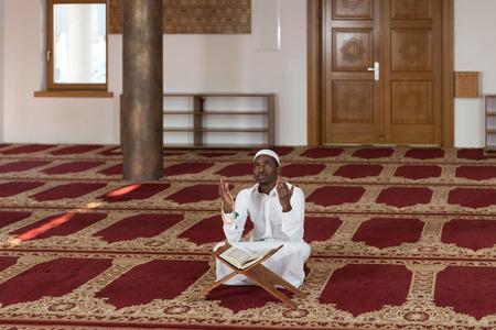 dishdasha: African Muslim Man Making Traditional Prayer To God While Wearing A Traditional Cap Dishdasha