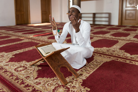 recitation: African Muslim Man Making Traditional Prayer To God While Wearing A Traditional Cap Dishdasha