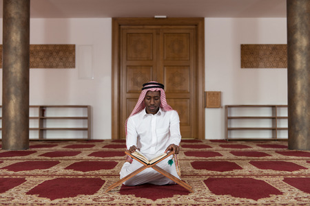 afro arab: Black African Muslim Man Making Traditional Prayer To God While Wearing A Traditional Cap Dishdasha Stock Photo
