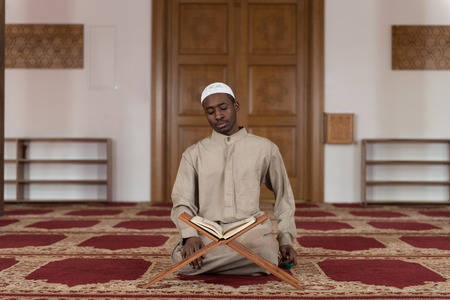 afro arab: Black African Muslim Man Reading Holy Islamic Book Koran