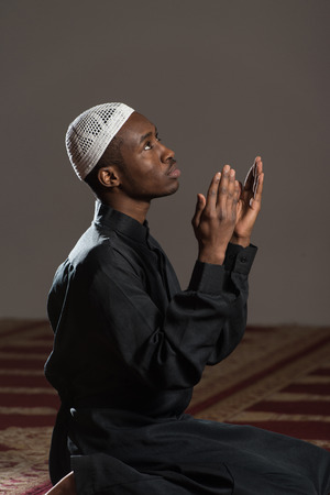 afro arab: African Muslim Man Making Traditional Prayer To God While Wearing A Traditional Cap Dishdasha