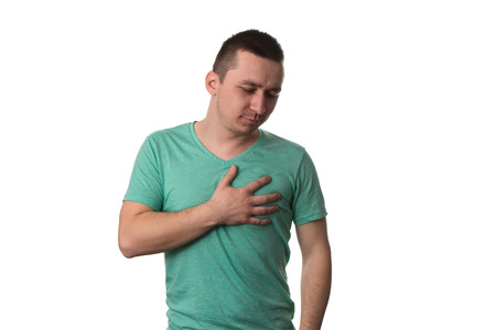 seizure: Young Man Holding A Hand To His Heart Due To This Pain - Over White Background Isolated