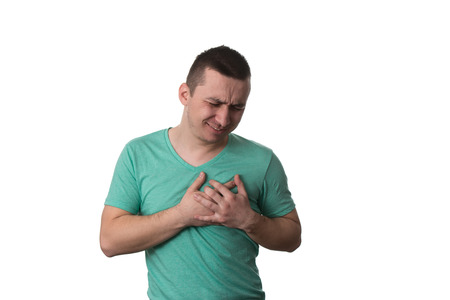 Young Man Holding A Hand To His Heart Due To This Pain - Over White Background Isolated