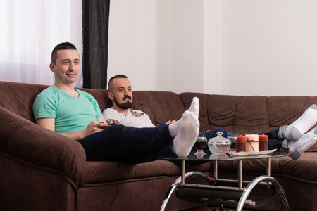 gamers: Two Young Gamers Sitting Together On Sofa And Playing Video Games At Home Stock Photo
