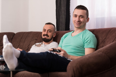 Two Young Gamers Sitting Together On Sofa And Playing Video Games At Home photo