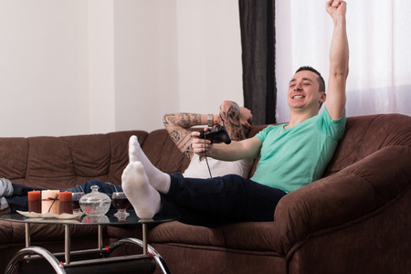 Two Young Gamers Sitting Together On Sofa And Playing Video Games At Home Standard-Bild