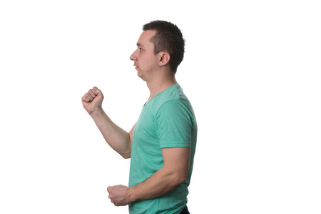 enrage: Portrait Of Angry Young Man Clenching His Fist - Isolated On White Background Stock Photo