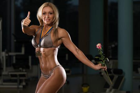 mujer con rosas: Edad Media Mujer en tacones altos con Medalla y rosas en la mano mostrando su cuerpo bien entrenado