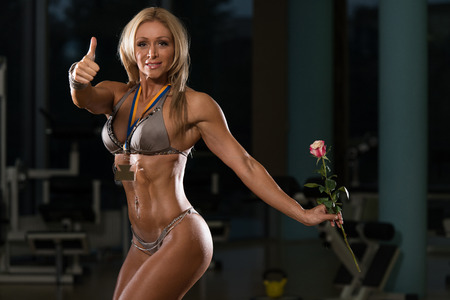 ragazze bionde: Medio Evo donna in tacchi alti con medaglia e Rose in mano mostrando il suo corpo ben allenato Archivio Fotografico